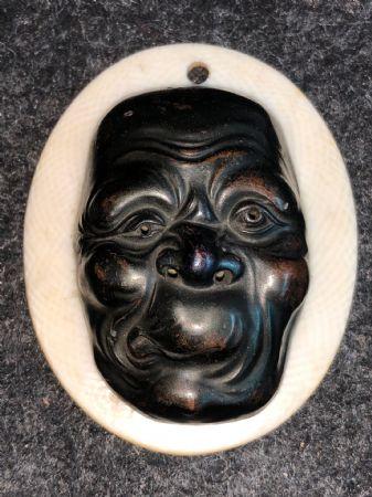 Piccola maschera con figura maschile grottesca in bronzo.Giappone