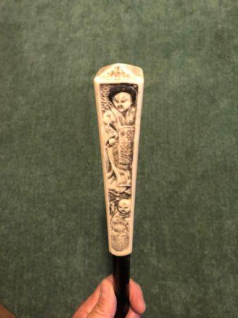 Bastone con pomolo in avorio a quattro facce con incisi personaggi orientali.Cina.