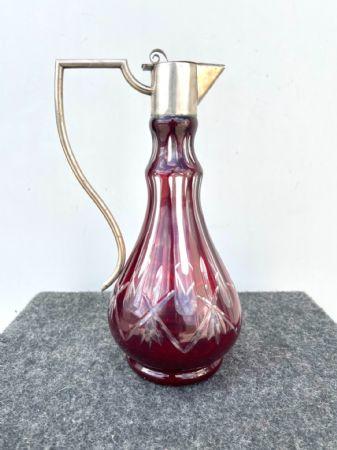 Bottiglia boemia incamiciata e molata con motivi geometrici.Collo e tappo in argento con punzone italiano.