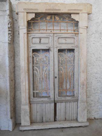 Portale liberty in pietra arenaria gialla con porta in legno