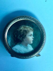 Miniatura sobre marfil que representa a un niño con marco de latón.