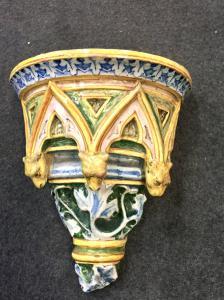 Mensola in maiolica decorata con losanghe,mascheroni e motivi vegetali in rilievo.Manifattura di Angelo Minghetti.Bologna.
