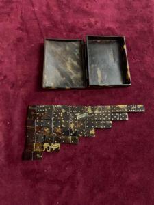 Caja en tratado que contiene fichas de juego de dominó