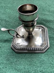 Candeliere 'bugia' in argento con decoro geometrico sulla base.Italia.