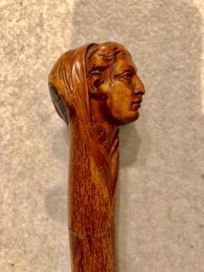 Kleben Sie ein Stück in Birkenholz mit einem Knopf, der eine weibliche Figur darstellt.