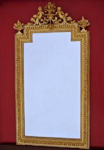 specchio frontone decorato con putti