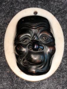 Small mask with grotesque bronze male figure.Japan