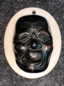Pequeña máscara con grotesca figura masculina de bronce.Japón