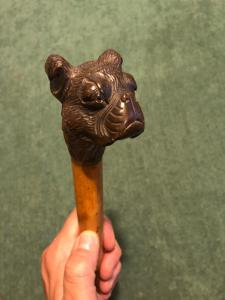 Stick with wooden knob depicting a dog's head. Barrel in rattan.