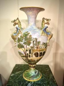 Par de vasos de faiança policromada decorados com paisagens e personagens (estilo Castelli). Alças laterais em forma de dragões. Angelo Minghetti. Bolonha.