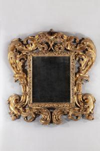 Espejo raro en madera tallada y dorada.