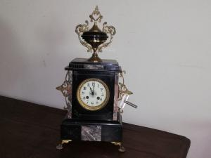 Elegant table clock in black marble and gilded bronzes in focus, working, central Italy neoclassical era