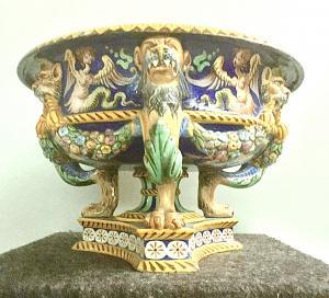 Peça central de majólica com taça redonda, pé trilobado e decoração grotesca e rafaelosa. Escolhida com gárgulas e motivos festões. Fabricação Ginori.