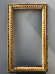 Cornice in legno intagliato e foglia oro.