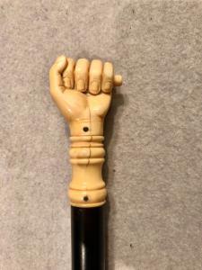 Halten Sie sich an den Elfenbeinknopf, der eine Hand zeigt, die eine Robbe hält.
