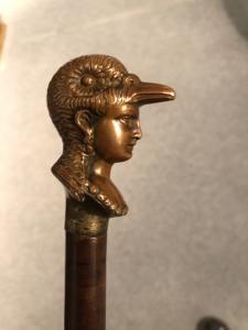 Abwehrstock mit massivem Bronzeknauf, der einen weiblichen Kopf mit einem vogelförmigen Helm darstellt.