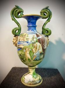 Vaso de majólica com entradas laterais de cobras e máscaras e decoração historiada. Fabricação de Minghetti. Bolonha.