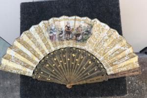 Ventaglio in tartaruga traforata e dorata con pavese in carta con stampe acquarellate con scene galanti.