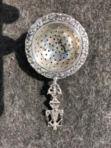 用普遍的字符和风格化植物主题装饰的银色滤锅荷兰。