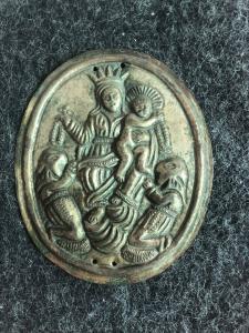 Mantel de latón que representa a la Virgen con el Niño y dos personajes encapuchados. Hermandad del Rosario.