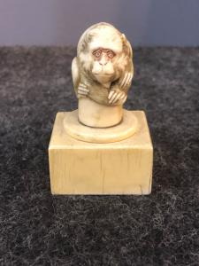 Small ivory sculpture depicting a squatting monkey on a square base. Japan.