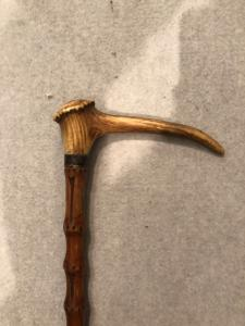 Animated stick with deer horn knob with corkscrew.