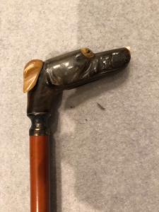 Stick with knob representing a greyhound dog head in horn.