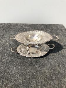银色双漏勺,带两个带有花卉装饰的手柄。意大利。