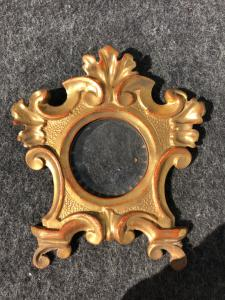Cornicina in legno intagliato e dorato con motivi vegetali e rocaille.