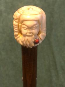Stick with ivory knob with coral and gold insert depicting an oriental character.