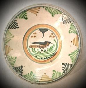 Prato de majólica com motivos vegetais estilizados na aba e um pássaro no umbo.Manifattura di Montelupo.