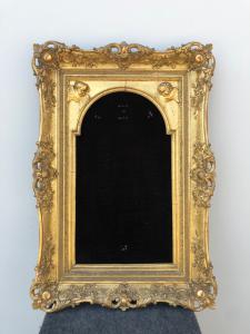 Cornice da Cristo in legno intagliato e foglia oro con applicazioni in stucco con decori floreali e putti.