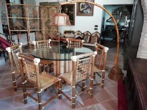 Particolare tavolo in bambù  con piano in cristallo, corredato da 6 sedie e piantana, ottime condizioni