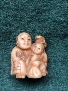 Ivory netsuke 'com figura sentada e criança com sapo na cabeça. Japão.
