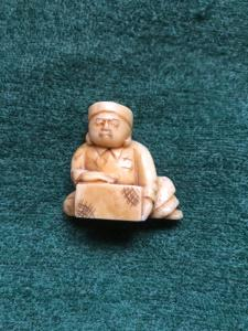 Ivory netsuke 'com figura sentada com tronco de madeira. Japão.