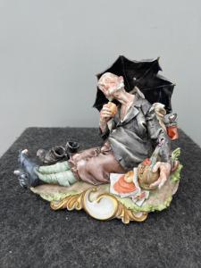 Scultura in porcellana policroma raffigurante personaggio caricaturale con ombrello e cibarie.Giuseppe Cappe'