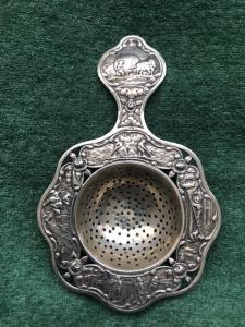 Colino da te' in argento con scene pastorali e floreali.Olanda.