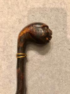 Stick in a single piece made of ebonized fruit wood with a knob representing a grotesque head.