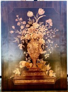 Pannello in legno intarsiato con decoro a vaso di fiori e frutta.