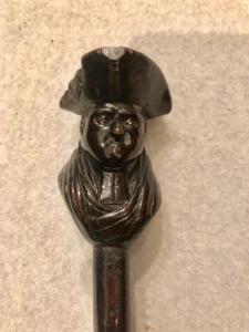 Bastone con pomolo in ebano raffigurante personaggio con cappello.