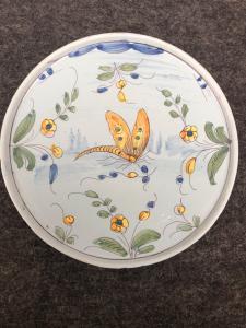 Piatto alzati ma in maiolica a sfondo berettino con farfalla.Pavia.