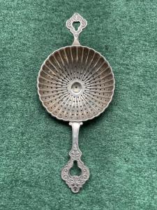 Colino da the in argento baccellato con motivi vegetali stilizzati.Germania.