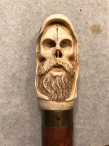 Stick mit Knochenknopf mit Totenkopf mit Kapuze und Bart.