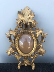 Piccola cornice a cartoccio in legno intagliato e foglia oro con motivi fogliati.