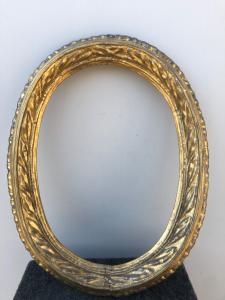 Cornice ovale in legno intagliato con motivo a foglie e foglia oro.