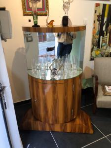 Bellissimo ed elegante mobile bar art Decò in radica di ulivo da centro. Sono presenti due specchi sopra l'anta per riporre le bottiglie.