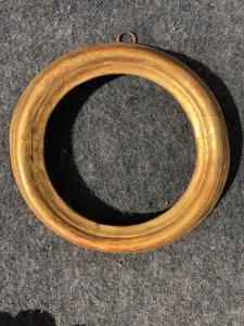 Cornice tonda in legno intagliato e dorato.