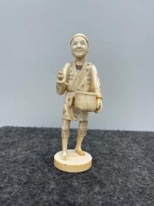 Okimono que representa a un granjero con una canasta y una pipa. Japón