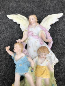 Bisque porcelain stoup with angel figure with outstretched wings protecting two children. France.
