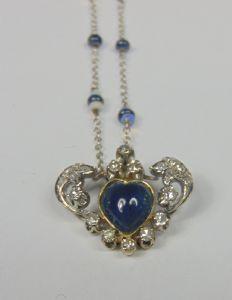 Collana in oro bianco con zaffiro a cabochon a forma di cuore, diamanti taglio brillante e piccoli opali nella catenina. Anni '40